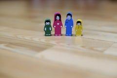 Mehrfarbige hölzerne Figürchen einer Familie mit zwei Kindern auf einem Bretterbodenhintergrund Eltern zusammen, Kinder vom diffe Stockfotografie