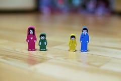 Mehrfarbige hölzerne Figürchen einer Familie mit zwei Kindern auf einem Bretterbodenhintergrund Vater mit Tochter, Mutter mit Soh Lizenzfreie Stockfotos