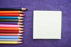 Mehrfarbige, helle, bunte Bleistifte für das Zeichnen gelegen auf dem links Stockfoto