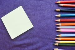 Mehrfarbige, helle, bunte Bleistifte für das Zeichnen gelegen auf dem Recht und ein Notizbuch Lizenzfreies Stockbild
