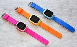 Mehrfarbige intelligente Uhr auf einem hellen Holztisch Beschneidungspfad eingeschlossen Stockbild