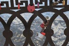 Mehrfarbige kleine Schlösser hängen am Zaun auf der Ufergegend Lizenzfreie Stockbilder