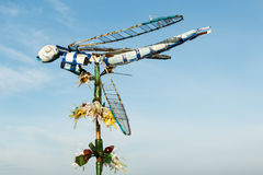 Mehrfarbige Libelle auf einer Blume gemacht von den Schrotten Wiederverwertung und überschüssiges Reduzierungskonzept Stockfotos