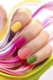 Mehrfarbige Maniküre mit rosa, Grünem, Gelbem und PfirsichNagellack stockbild