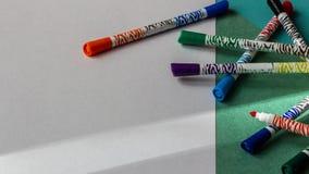 Mehrfarbige Markierungen liegen auf dem Hintergrund der farbigen Pappe und der Weißbuchnahaufnahme lizenzfreie stockfotos