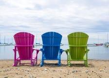 Mehrfarbige Muskoka-Häuschen-Strandstühle auf dem Sand, der heraus zum Hafen schaut Lizenzfreies Stockbild