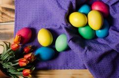 Mehrfarbige Ostereier in einem Korb auf einem hölzernen Hintergrund stockbild