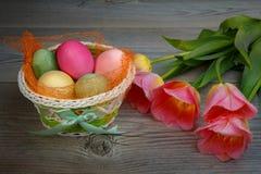 Mehrfarbige Ostereier und Bonbons in einem schönen Korb stockfoto