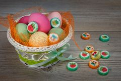 Mehrfarbige Ostereier und Bonbons in einem schönen Korb stockfotografie