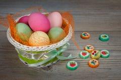 Mehrfarbige Ostereier und Bonbons in einem schönen Korb stockbilder