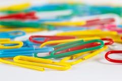 Mehrfarbige Papierklammern auf weißer Tischplattennahaufnahme Stockfotografie