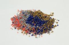 Mehrfarbige Perlen in den Glasgef??en Perlen werden auf einen wei?en Hintergrund gegossen Mehrfarbige Plastikpolymere Plastik-pil lizenzfreie stockbilder