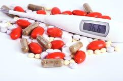 Mehrfarbige Pillen und Nahaufnahme mit 36,6 Thermometern Stockbilder