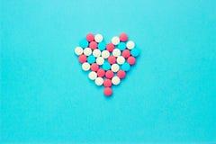 Mehrfarbige Pillen von den wei?en Gl?sern auf einem blauen Hintergrund stockfoto