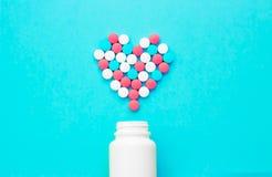 Mehrfarbige Pillen von den wei?en Gl?sern auf einem blauen Hintergrund lizenzfreies stockbild