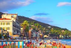 Mehrfarbige Regenschirme auf dem Strand in Alassio, Provinz von Savona, Sanremo-Region, Italien Stadt am Sonnenuntergang Lizenzfreie Stockfotografie