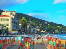Mehrfarbige Regenschirme auf dem Strand in Alassio, Provinz von Savona, Sanremo-Region, Italien Stadt am Sonnenuntergang Stockbilder