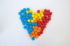 Mehrfarbige runde S??igkeitsdrag?es ausgebreitet in Form eines Herzens auf einem wei?en Hintergrund stockbilder