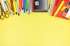 Mehrfarbige Stifte, Bleistifte, Markierungen und Scheren auf gelber Tabelle Stockfotos