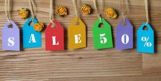 Mehrfarbige Tags, die Verkauf 50% mit Papierblumen auf Holz beschriften. Stockbilder