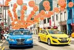 Mehrfarbige Taxis, die auf Südbrücken-Straße in Singapur fahren Stockbild
