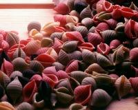 Mehrfarbige Teigwaren auf hölzerner Platte stockfotos