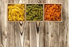 Mehrfarbige Teigwaren in Form von Spiralen liegen in den quadratischen Holzkisten, die auf einer Tabelle stehen stockfotos