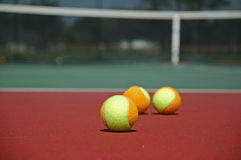 Mehrfarbige Tennis-Kugeln auf hartem Gericht lizenzfreies stockfoto