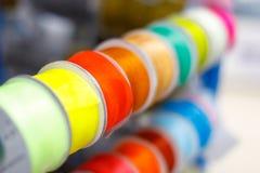 Mehrfarbige Textilbänder in den handgemachten Spulen angezeigt für Verkauf im Speicher lizenzfreie stockfotos