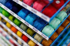 Mehrfarbige Textilfaden in den handgemachten Spulen werden f?r Verkauf im Speicher angezeigt lizenzfreies stockfoto