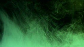 Mehrfarbige Tinte fällt in Wasser auf dunklem Hintergrund Stockbild