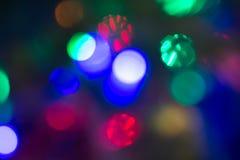 Mehrfarbige unscharfe Lichter von Seifenblasen einer neues Jahr ` s Girlande und Fliegens als schönen Hintergrund Lizenzfreie Stockfotos