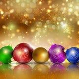 Mehrfarbige Weihnachtsbälle auf einem Goldhintergrund Lizenzfreies Stockfoto