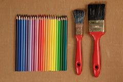Mehrfarbige Zeichenstifte und zwei benutzte Bürsten Stockfotos