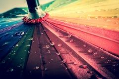 Mehrfarbiger bunter Regenschirm mit allen Farben des Regenbogens mit Regentropfen lizenzfreies stockbild