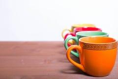 Mehrfarbiger keramischer Schalenstand am Rand eines Holztischs stockfoto