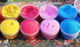 Mehrfarbiger Sand in den Plastikdosen Verwendet für Handwerkstraining Lizenzfreie Stockfotos
