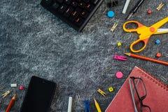Mehrfarbiger Schulbedarf auf schwarzem und gelbem Tafelhintergrund mit Kopienraum stockfotografie