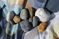 Mehrfarbiger Stein auf farbigem Gewebe stockfoto