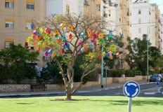 Mehrfarbiger Vogelhausfall auf einem Baum Stockfotografie