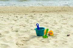 Mehrfarbiges children' s-Spielwaren im Sand durch das Meer lizenzfreie stockfotos