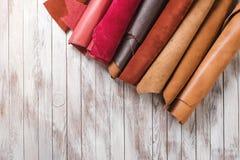 Mehrfarbiges Leder in den Rollen auf hölzernem Hintergrund Stockbilder