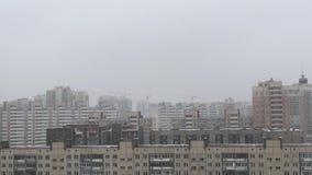 Mehrstöckige Häuser während Schneefälle im Winter im wolkigen Wetter stock video footage