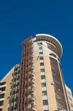 Mehrstöckiges Haus des modernen Ziegelsteines auf tiefem BAC des blauen Himmels Lizenzfreies Stockbild
