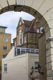 Mehrstufiges Haus des Ziegelsteines mit gro?en sch?nen Fenstern Foto gemacht durch den alten Bogen Zentraler Bezirks-Ansicht Lond stockfoto