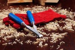 Meißel, rote Handschuhe und Holz Lizenzfreies Stockbild