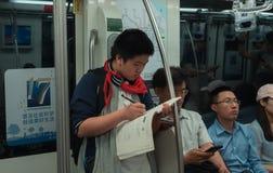 28 Mei, 2018, de stad van Shanghai, China De Chinese schooljongen doet zijn thuiswerk op weg naar huis in metrovervoer royalty-vrije stock afbeelding