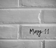` 11 mei ` OP WITTE DUIDELIJKE BAKSTENEN MUUR wordt GESCHREVEN die Stock Foto