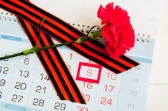 9 Mei - rode anjer met George lint die op de kalender met 9 Mei-datum liggen Royalty-vrije Stock Foto's