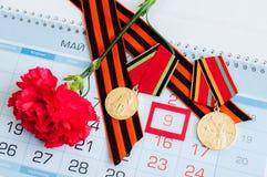 9 Mei - rode anjer met George van oorlogsmedailles lint die op de kalender met 9 Mei-datum liggen Royalty-vrije Stock Afbeelding